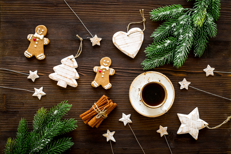 New Year composition with sweets. Gingerbread cookies in shape of man, spruce, star near coffee, spruce branch, festive decoration on black background top view