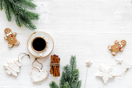 New Year composition with sweets. Gingerbread cookies in shape of man, spruce, star near coffee, spruce branch, festive decoration on white background top view.