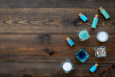 Dead sea cosmetics layout. Sea salt in bottles and bowls near small shells on dark wooden background top view copy space Archivio Fotografico
