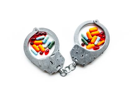 Arresto per concetto illegale di acquisto, possesso e vendita di droghe. Droghe come pillole vicino a manette su sfondo bianco vista dall'alto. Archivio Fotografico