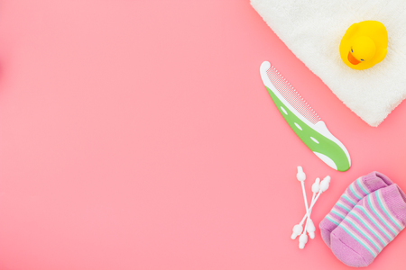 Baby care. Bath cosmetics and accessories for child with towel and yellow rubber duck on pink background top view.