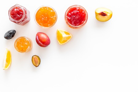 Jams different tastes made of fruits and berries near pieces of fruits on white background top view.