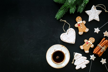 New Year composition with sweets. Gingerbread cookies in shape of man, spruce, star near coffee, spruce branch, festive decoration on black background top view. Foto de archivo