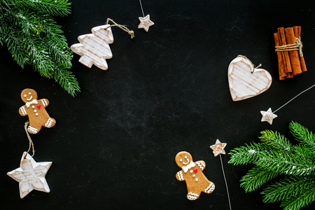 New Year composition with sweets. Gingerbread cookies in shape of man, spruce, star near coffee, spruce branch, festive decoration on black background top view. 版權商用圖片