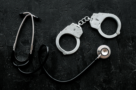 Medical lawsuit. Arrest for medical crime concept. Handcuff near stethoscope on black background top view.