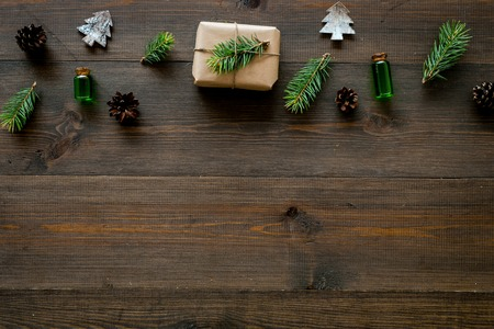 New Year pattern with pine sprigs, cones, spruce figure, fir oil and new year gift decorated with craft paper and pine sprout on dark wooden background top view. Stock Photo