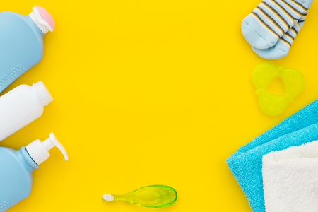 Childrens personal care kit. Bath accessories with teeth brush on yellow background top view.