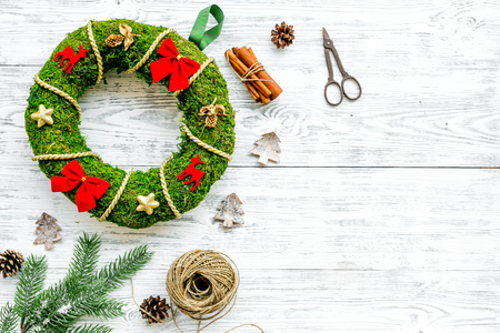 Christmas decoration concept. Traditional green christmas wreath near matherials and instruments, sciccors on white wooden background top view. Stock Photo