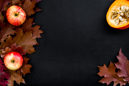 Composition with autumn vegetables and leaves in red and orange colors. Brown dried leaves, pumpkin, apple on black background top view. Stock Photo