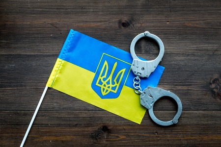 Violation of law, law-breaking concept. Metal handcuffs on Ukrainian flag top view. Stock Photo