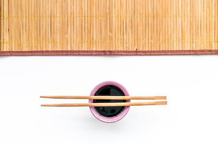 Chinese meal concept. soy sauce in bowl near chopsticks and bamboo table mat on white background top view. Zdjęcie Seryjne