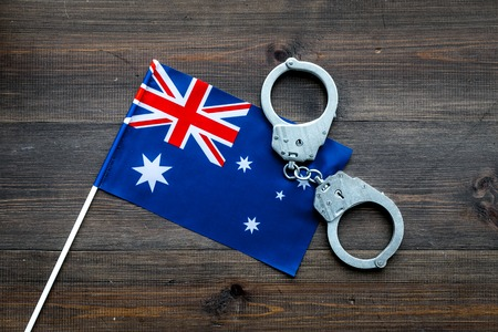 Violation of law, law-breaking concept. Metal handcuffs on Australian flag top view.