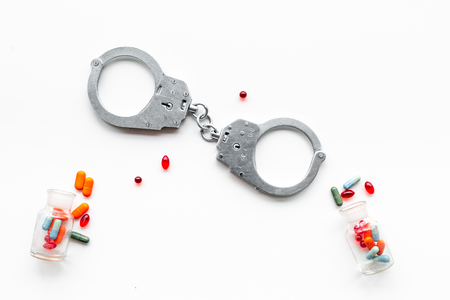 Arrest for illegal purchase, possession and sale drugs concept. Drugs as pills near handcuff on white background top view.