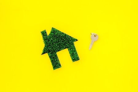 Eco friendly technologies for home concept. House silhouette made of green grass on yellow background top view space for text