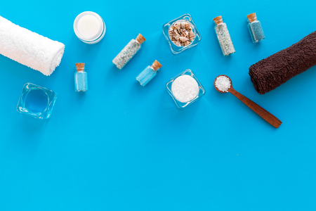 Sea salt for spa and aroma spa cosmetics near towel and shells on blue background top view.