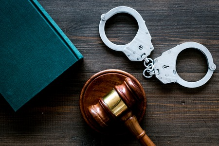 Crime concept. Metal handcuffs near judge gavel and law book on dark wooden background top view.