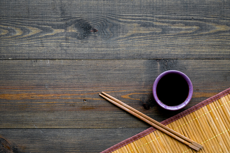 Chinese meal concept. soy sauce in bowl near chopsticks and bamboo table mat on dark wooden background top view copy space pattern Banque d'images