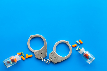 Arrest for illegal purchase, possession and sale drugs concept. Drugs as pills near handcuff on blue background top view copy space Stok Fotoğraf - 112015782
