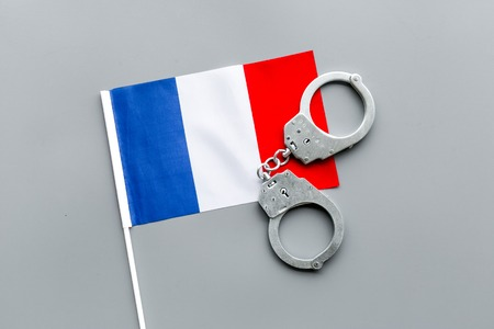 Violation of law, law-breaking concept. Metal handcuffs on French flag on grey background top view 스톡 콘텐츠