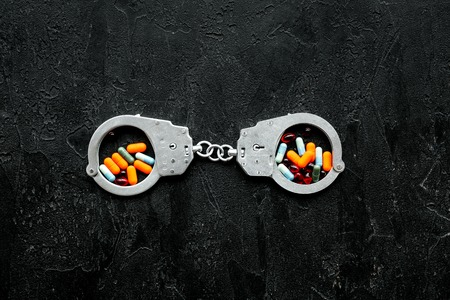 Arrest for illegal purchase, possession and sale drugs concept. Drugs as pills near handcuff on black background top view. Stock fotó