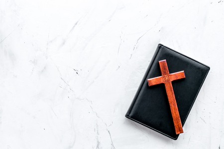 Farewell ceremony, funeral concept. Wooden cross on Bible on white stone background top view copy space Zdjęcie Seryjne - 112080905