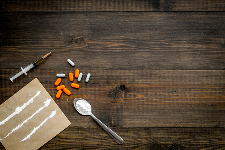 Take drugs, drugs addiction concept. White powder like heroine or cocaine, drug tracks pills, spoon, syringe on dark wooden background top view space for text Reklamní fotografie