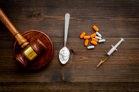 Drugs addiction, arrest for drugs. Pills, spoon with powder, syringe on dark wooden background top view