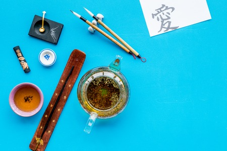 Chinese or japanese traditions. Calligraphy and tea ceremony concept. Special writting pen, ink near teapot and cup of tea, insense on blue background top view copy space