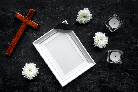 Funeral. Mockup of portrait of the deceased, of dead person. Frame with black ribbon near flowers, candles and cross on black background top view