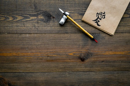Chinese traditional calligraphy concept. Asian hieroglyph symbol in craft paper notebook near special writting pen on dark wooden background top view copy space Stok Fotoğraf