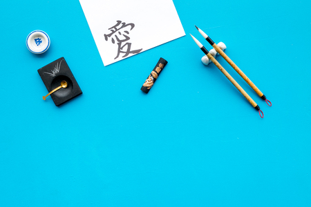 Chinese or japanese calligraphy concept. Hieroglyph near traditional written accessories on blue background top view copy space