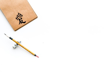 Chinese traditional calligraphy concept. Asian hieroglyph symbol in craft paper notebook near special writting pen on white background top view space for text
