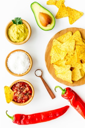 Popular mexican snack nachos. Tiangle nacho tortilla near salsa and guacamole sause, chili pepper, salt on white background top view