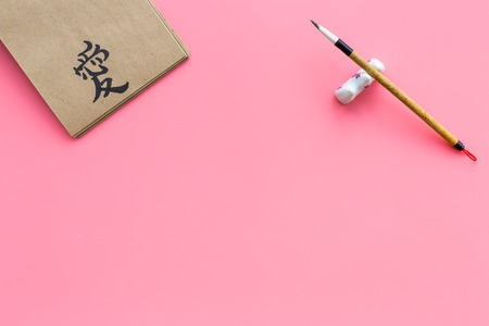 Chinese traditional calligraphy concept. Asian hieroglyph symbol in craft paper notebook near special writting pen on pink background top view copy space