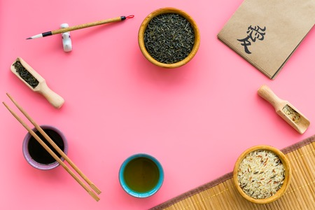 Chinese traditional symbols concept. Tea, rice, hieroglyph symbol, bambootabe mat, chopsticks, soy sause on pink background top view frame copy space