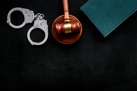Arrest concept. Metal handcuffs near judge gavel and law book on black background top view. 스톡 콘텐츠 - 112138819