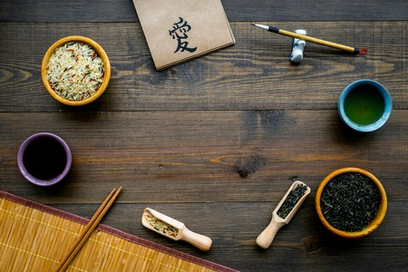 Chinese traditional symbols concept. Tea, rice, hieroglyph symbol, bambootabe mat, chopsticks, soy sause on dark wooden background top view frame copy space