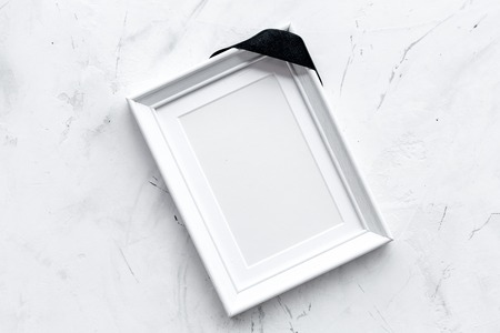 Death concept. Photo frame, mockup with black ribbon on white background top view copy space