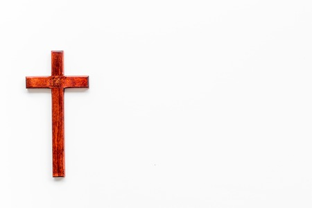 Funeral concept. Wooden cross on white background top view copy space
