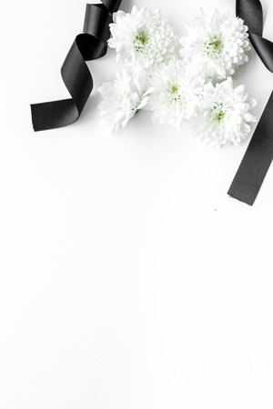 Funeral symbols. White flower near black ribbon on white background top view copy space 写真素材