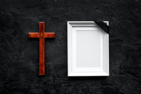 Funerale. Mockup di ritratto del defunto, di persona morta. Cornice con nastro nero vicino a croce su sfondo nero vista dall'alto copia spazio