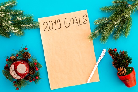 Goals list for New Year 2019 mockup near new year background like spruce branch, candle, festive tree on blue background top view