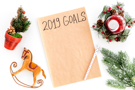 Goals list for New Year 2019 mockup near new year background like spruce branch, candle, festive tree, toy horse on white background top view