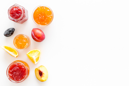 Jams different tastes made of fruits and berries near pieces of fruits on white background top view space for text 스톡 콘텐츠
