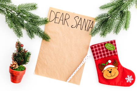 Letter to Santa Claus template. Mockup on craft paper with text Dear Santa near Christmas decoration like fir branches, festive tree, socks on white background top view