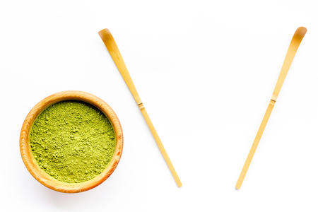 Matcha powder in bowl near specail stick on white background top view copy space