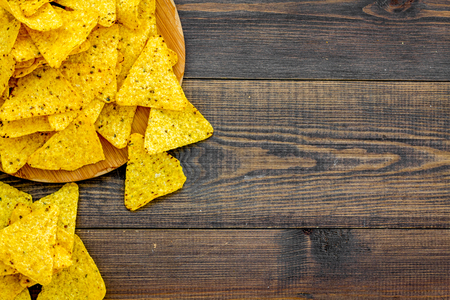 Mexican snack. Make nachos. Crispy nachos on wooden cutting board on dark wooden background top view copy space
