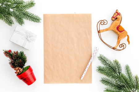 New Year or Christmas mockup. Template for letter to Santa, list of plans and goals for New Year, wishlist near fir branches, gift box, toy horse on white background top view