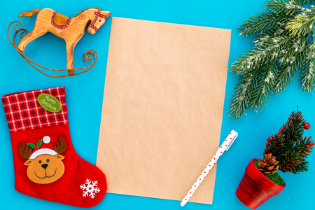 New Year or Christmas mockup. Template for letter to Santa, list of plans and goals for New Year, wishlist near fir branches, Christmas socks on blue background top view Stock Photo