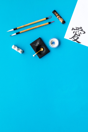 Chinese or japanese calligraphy concept. Hieroglyph near traditional written accessories on blue background top view.